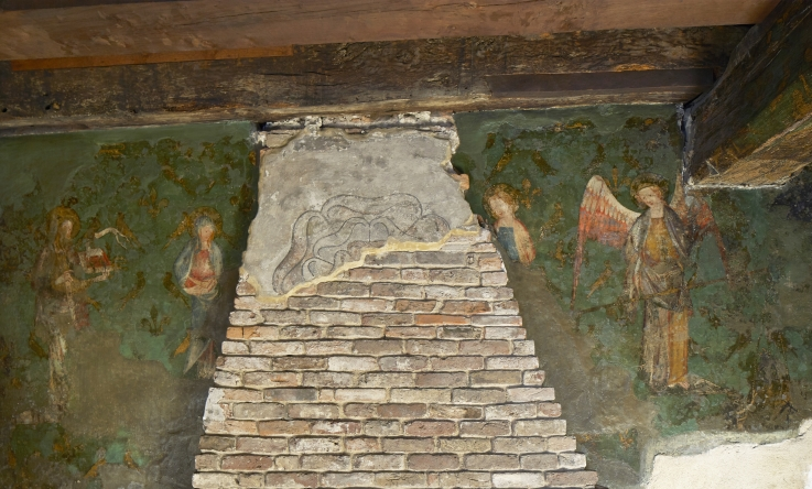 The medieval wall painting depicting four saints, and, in the centre, a faded Tudor rose painted onto a chimney breast. Tower of London. Photograph: © Historic Royal Palaces