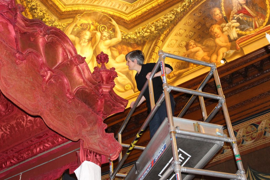 Conservation Supervisor Rebecca Bissonnet examining the cornices and corbels before de-installation
